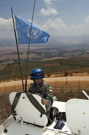 "UNIFIL Indonesian UNIFIL peacekeeper atop armoured personnel carrier next to the Israeli ""Technical Fence"" along the Blue Line at Kafer Kila, South Lebanon. 28 August 2009. Pasqual GORRIZ/UNIFIL"